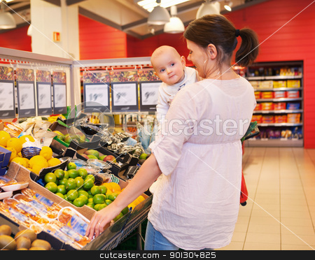 Mother and Baby in Grocery Store stock photo, Mother carrying child while shopping in supermarket by Tyler Olson