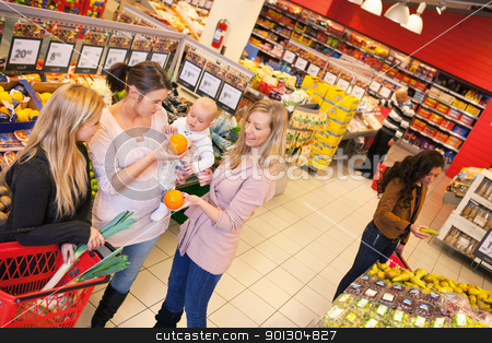 Mother and Friends in Grocery Store stock photo, High angle view of mother carrying child with friends shopping in supermarket by Tyler Olson