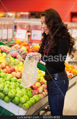 Young woman buying fruits stock photo, Young woman buying fruits in the supermarket by Tyler Olson