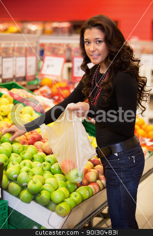 Young Woman Buying Fruit stock photo, Young woman smiling while buying fruits in the supermarket by Tyler Olson