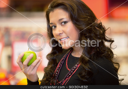 Closeup of a young woman holding apple stock photo, Closeup of a young woman holding apple in the supermarket by Tyler Olson