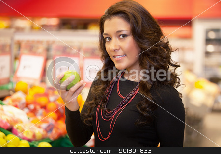 Woman Buying Fruit stock photo, Portrait of a young woman holding apple in the supermarket by Tyler Olson