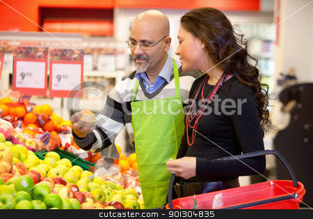Grocer and Customer stock photo, Shop assistant holding apple with customer in the supermarket by Tyler Olson