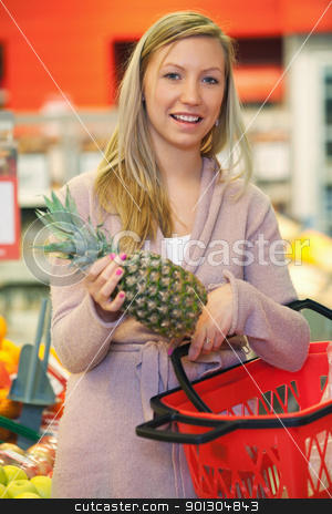 Woman with Pineapple stock photo, Cheerful young woman holding pineapple with basket in the supermarket by Tyler Olson