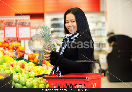 Asian Woman Buying Fruit stock photo, Portrait of a cheerful young woman buying fruits in the supermarket by Tyler Olson