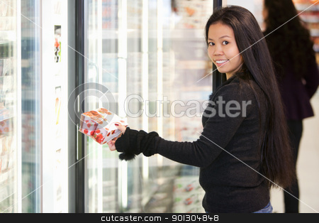Woman Buying Yogurt stock photo, Portrait of a young woman holding box in front of refrigerator in the supermarket by Tyler Olson