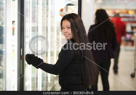 Young woman smiling while opening refrigerator in supermarket stock photo, Young woman smiling while opening refrigerator in supermarket with people in the background by Tyler Olson