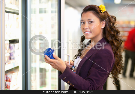 Woman by Grocery Store Fridge stock photo, Portrait of a young woman holding container in front of refrigerator in the supermarket by Tyler Olson