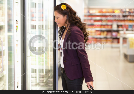 Young woman opening refrigerator stock photo, Young woman opening refrigerator in the supermarket by Tyler Olson