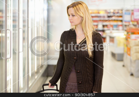 Supermarket Shopping Woman stock photo, Young woman looking at goods in refrigerator section of supermarket by Tyler Olson
