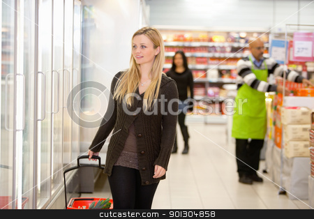 Cold Food at Grocery Store stock photo, Smiling woman walking in shopping centre, looking in refrigerator with people in the background by Tyler Olson