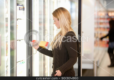 Woman Buying Juice from Cooler stock photo, Beautiful young lady purchasing a product at a grocery store with person in the background by Tyler Olson