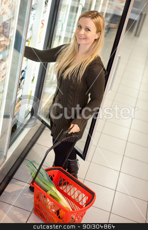 Cold Food Grocery Store Woman stock photo, Smiling woman in a supermarket standing in front of the cooler looking at camera by Tyler Olson
