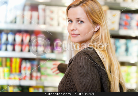 Grocery Store Woman stock photo, Close-up of woman reaching for products arranged in refrigerator and looking at camera by Tyler Olson