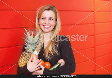 Woman with Fuit and Vegetables stock photo, Smiling woman leaning against red wall while holing fruits and vegetables by Tyler Olson