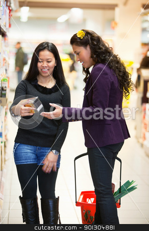 Woman in a store looking at a product stock photo, Smiling women looking at a product in a shopping store with people in the background by Tyler Olson