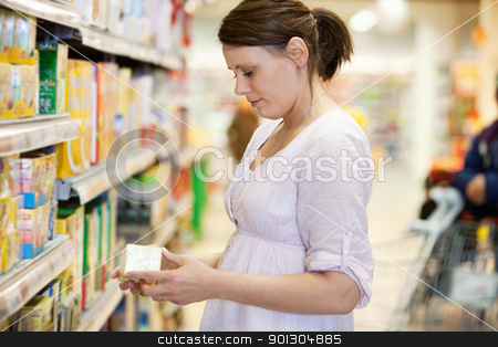 Shopping Woman in Supermarket stock photo, Mid adult woman looking at a product in shopping store with person in the background by Tyler Olson