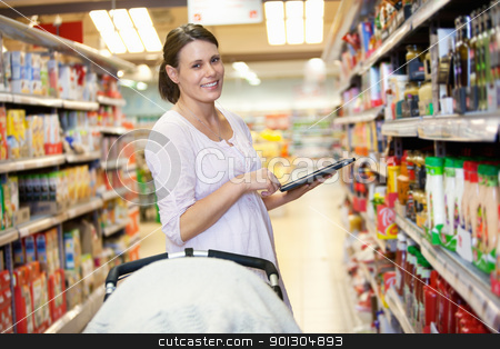 Mother with Electronic Shopping List stock photo, Woman holding digital tablet with baby stroller in foreground while looking at camera in shopping centre by Tyler Olson