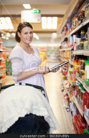 Woman with Shopping List on Tablet Computer stock photo, Woman holding digital tablet with baby stroller in foreground while looking at camera in shopping centre by Tyler Olson