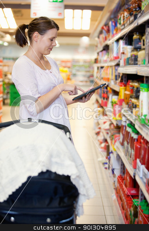 Woman holding digital tablet in shopping centre stock photo, Mid adult woman holding digital tablet in shopping centre with baby stroller in foreground by Tyler Olson