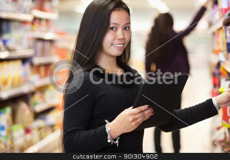 Woman with Tablet Computer Shopping List stock photo, Portrait of woman looking at the products while using digital tablet in shopping centre with person in background by Tyler Olson