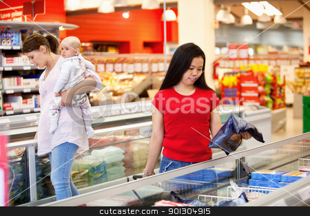 Women shopping in grocery store stock photo, Woman and baby in grocery store with another female in foreground by Tyler Olson