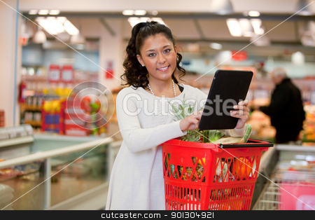 Woman using Tablet Computer in Supermarket stock photo, A happy woman using a tablet computer for a grocery list in a supermarket by Tyler Olson