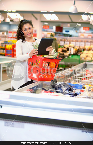 Woman with Electronic Shopping List stock photo, Shopper with basket holding shopping list on digital tablet and looking at camera by Tyler Olson