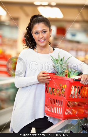 Woman Portrait in Supermarket stock photo, Smiling woman holding basket filled with fruits in supermarket and looking at camera by Tyler Olson