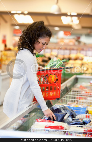 Woman Buying Frozed Food in Supermarket stock photo, Young woman with red basket buying frozen food in supermarket by Tyler Olson