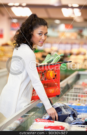 Woman Buying Frozen Food  stock photo, Young smiling woman buying frozen food in grocery store by Tyler Olson