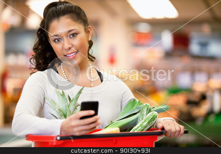 Woman with Shopping List on Phone stock photo, Smiling young woman using mobile phone while shopping in shopping store and looking at camera by Tyler Olson