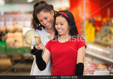 Friends in Supermarket stock photo, Smiling young women using mobile phone in shopping centre by Tyler Olson
