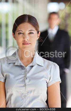 Young attractive businesswoman stock photo, Portrait of an young attractive businesswoman with man standing in background by Tyler Olson