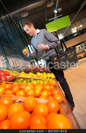 Man in Supermarket Buying Fruit stock photo, Man carrying basket while buying fruits in the supermarket by Tyler Olson