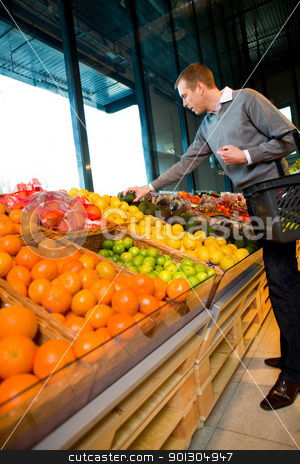 Buying Fruit and Vegetables stock photo, A man in a grocery store buying fruits and vegetables by Tyler Olson