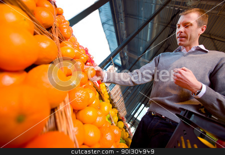 Grocery Store Orange stock photo, A man with a basket buying oranges and fruit at a grocery store by Tyler Olson