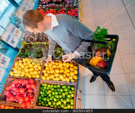 Male in Supermarket Buying Fruit stock photo, High angle view of a man carrying basket while buying fruits in the supermarket by Tyler Olson
