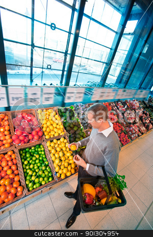 Grocery Store Shopping stock photo, A young adult male buying fruits and vegetables in a supermarket by Tyler Olson