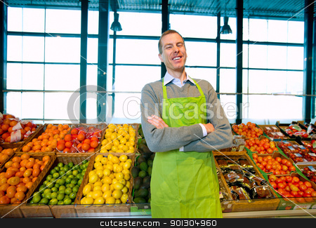 Grocery Store Owner stock photo, A grocery store owner standing in front of vegetables and fruit by Tyler Olson