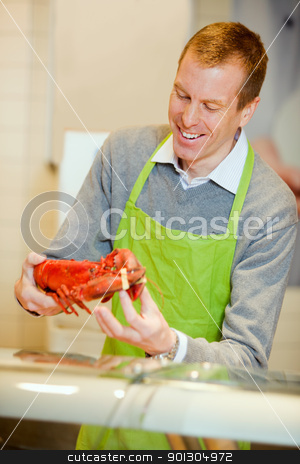 Fish Counter with Lobster stock photo, A grocery store worker with a lobster at the fish counter by Tyler Olson
