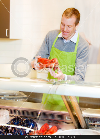 Lobster at Grocery Store stock photo, A fresh fish counter in a grocery store - clerk with a lobster by Tyler Olson
