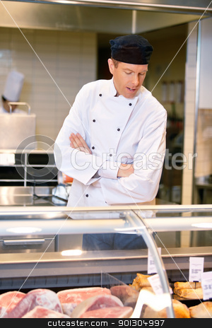 Butcher at Meat Counter stock photo, A butcher looking at the available meat in a grocery store by Tyler Olson