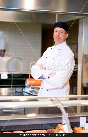 Butcher Portrait stock photo, A butcher standing behind a fresh meat counter by Tyler Olson