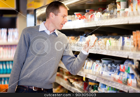 Grocery Store Man stock photo, A man buying cheese and comparing prices in a grocery store by Tyler Olson
