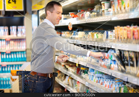Man Shopping in Grocery Store stock photo, A happy man smiling and shopping with basket in grocery store. by Tyler Olson