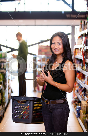 Asian Woman in Supermarket stock photo, Portrait of a happy asian woman in a supermarket with a smart phone shopping list by Tyler Olson