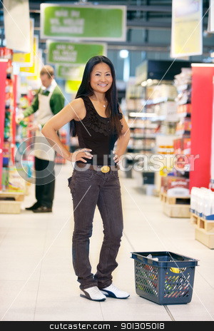 Portrait of Asian Woman in Grocery Store stock photo, Full length of smiling asian woman looking at camera with hands on waist and man in the background by Tyler Olson