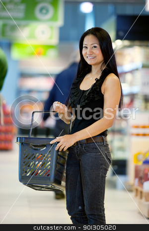 Happy Asian Female Shopper stock photo, A happy female asian woman with grocery basket in supermarket by Tyler Olson