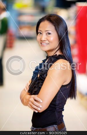 Asian Woman in Grocery Store stock photo, Confident smiling asian woman with arms crossed in shopping centre looking at camera by Tyler Olson